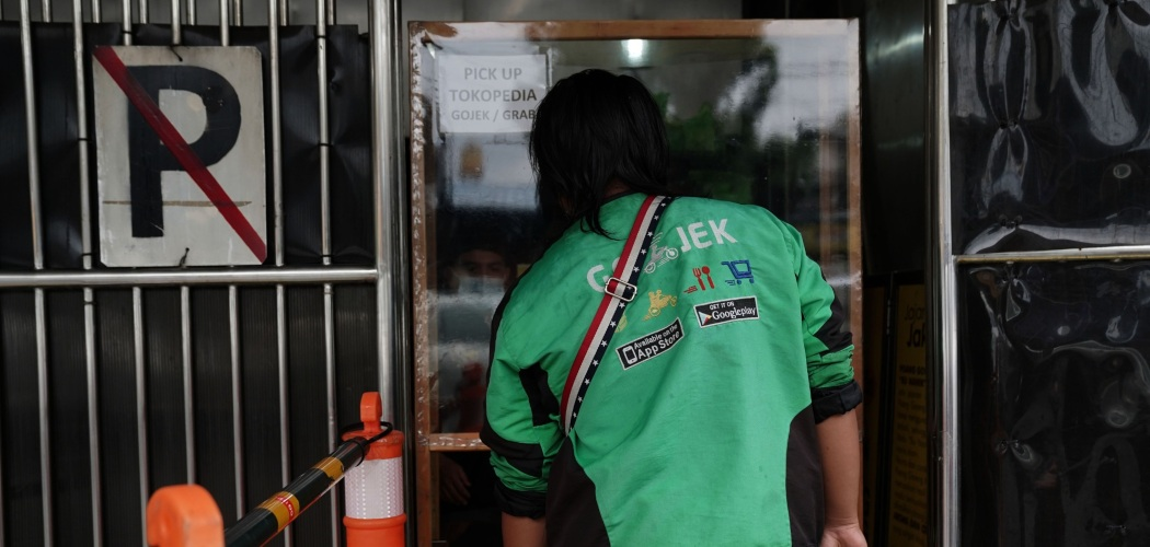 Pengemudi Gojek mengambil pesanan makanan di Jakarta, Indonesia, Selasa (5/1/2021). - Bloomberg/Dimas Ardian