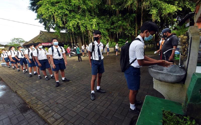 Siswa mencuci tangan saat akan memasuki area sekolah dalam pembelajaran tatap muka (PTM) di SMP Negeri Hindu 2 Sukawati, Gianyar, Bali, Selasa (23/3/2021).  - Antara/Nyoman
