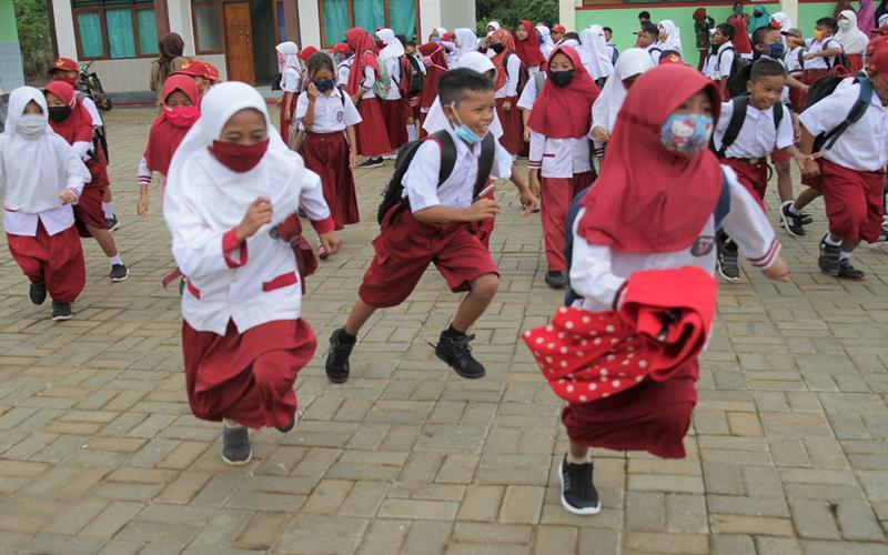 Sejumlah murid berlari memasuki ruang kelas di SD Negeri 1 Praja Taman Sari di Desa Wonuamonapa, Konawe, Sulawesi Tenggara, Senin (13/7 - 2020). Pihak sekolah terpaksa menerapkan pembelajaran dengan tiga kali pertemuan tatap muka di sekolah dalam sepekan karena terbatasnya jaringan telekomunikasi untuk penerapan pembelajaran jarak jauh secara daring guna mencegah penyebaran COVID/19. ANTARA FOTO