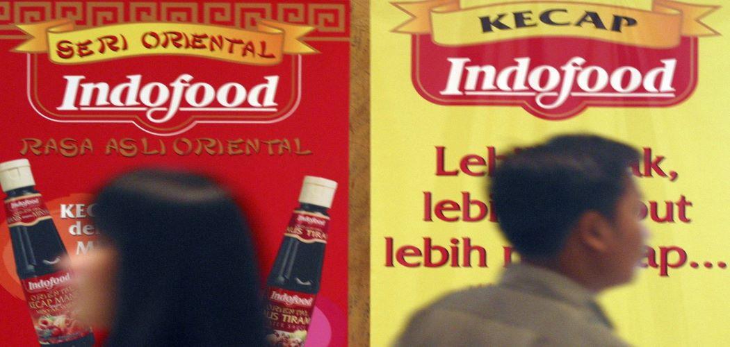 Pejalan kaki melintas di depan iklan Indofood 2003. - Bloomberg / Josh Estey