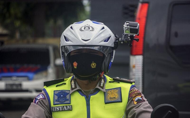 Polisi Lalu Lintas menggunakan helm yang dilengkapi kamera portabel pengawas tilang elektronik di Traffic Management Centre (TMC) Polres Pekalongan, Jawa Tengah, Selasa (23/3/2021). - Antara/Harviyan P.