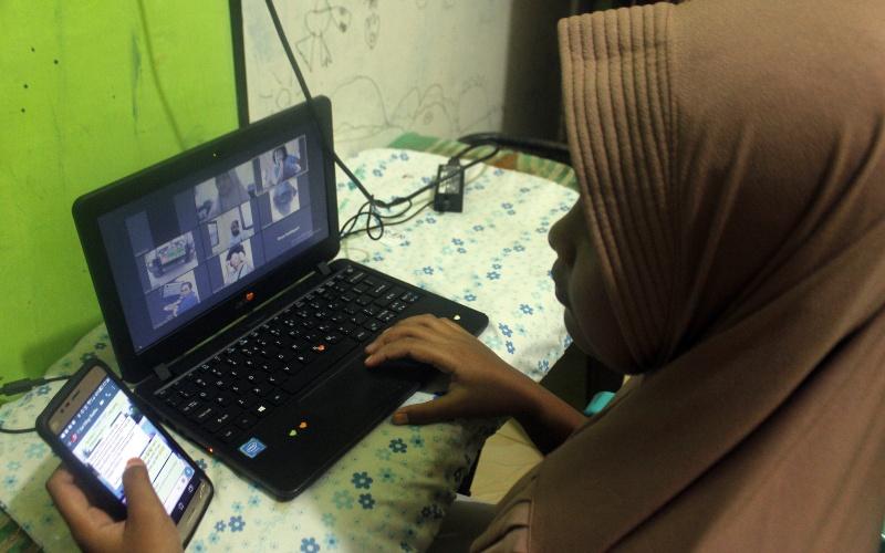 Warga saat melakukan rapat daring menggunakan layanan internet di Kota Sorong, Papua Barat, Minggu (29/3/2020). - ANTARA FOTO/Olha Mulalinda