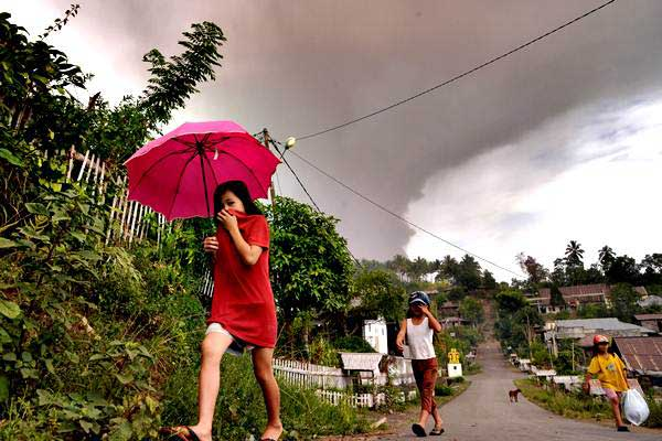Warga berjalan di bawah hujan abu vulkanik setinggi 5.809 mdpl berwarna kelabu akibat letusan gunung Soputan, di atas Desa Kota Menara, Minahasa Selatan, Sulawesi Utara, Rabu (3/10/2018). - ANTARA/Adwit B Pramono