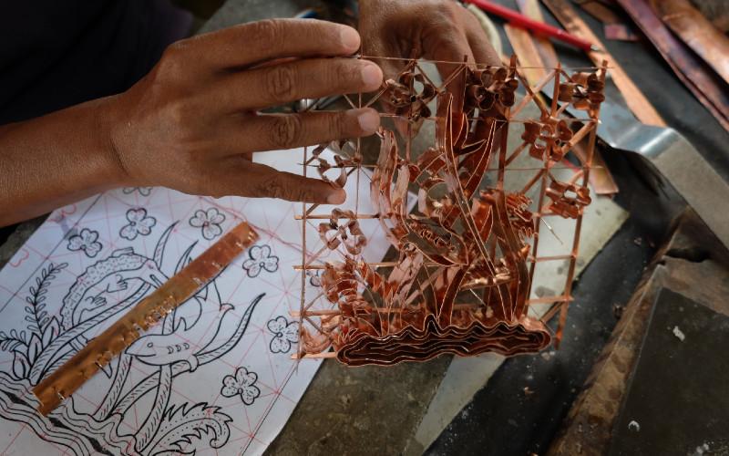 Pekerja membuat alat cap batik di Sondakan, Laweyan, Solo, Jawa Tengah, Rabu (26/8/2020). Alat cap batik berbahan tembaga tersebut dijual seharga Rp300.000 hingga jutaan rupiah tergantung kualitas bahan dan tingkat kerumitan motif. - Antara