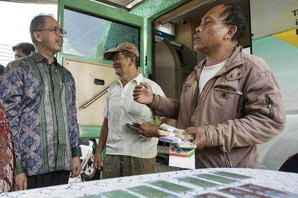 Deputi Gubernur Bank Indonesia Sugeng (kiri) berbincang dengan nasabah yang melakukan penukaran uang Rupiah pecahan kecil di Lapangan IRTI Monas, Jakarta Pusat, Rabu (7/6). - Antara/Widodo S Jusuf