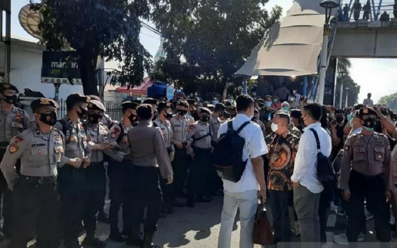 Petugas Kepolisian menghalau tim kuasa hukum yang memaksa masuk ke dalam gedung Pengadilan Negeri Jakarta Timur, Jumat (26/3/2021). - Antara \r\n