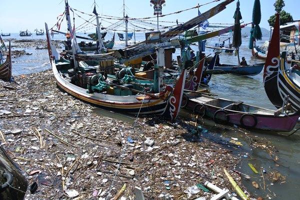 Nelayan melintasi muara sungai yang tercemar sampah plastik di Pantai Satelit, Desa Tembokrejo, Muncar, Banyuwangi, Jawa Timur, Jumat (19/4/2019). produksi sampah plastik di Indonesia telah mencapai 64 juta ton/tahun dan sebagian besar mencemari lautan. - Antara/Seno
