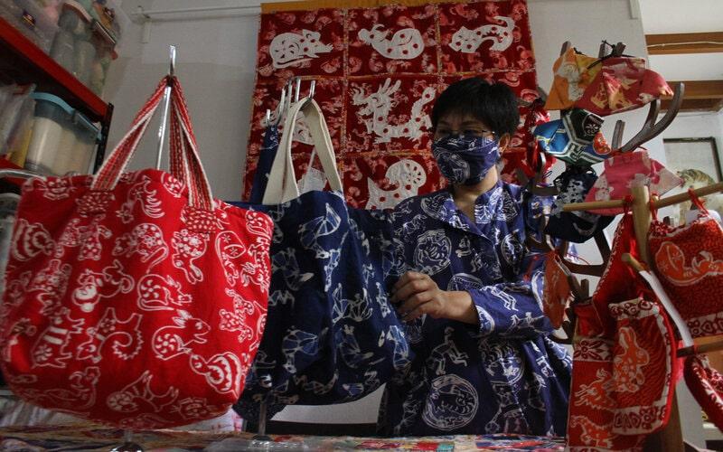 Desainer Lusiana Limono menata tas batik shio hasil karyanya yang dicetak dari origami atau seni melipat kertas di Studio Kait Handmade, Malang, Jawa Timur, Kamis (11/2/2021). Berbagai produk turunan batik shio yang dibuat dengan cetakan origami tersebut dijual ke berbagai kota melalui pasar digital dengan harga Rp25.000 hingga Rp2,5 juta per buah tergantung ukuran dan jenis produknya. - Antara/Ari Bowo Sucipto.