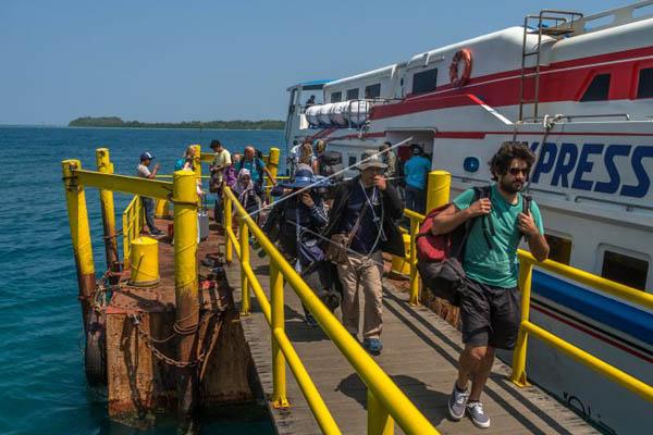 Wisatawan berjalan di dermaga setelah kapal yang mereka tumpangi tiba di Pulau Karimunjawa, salah satu destinasi utama di Kabupaten jepara, Jawa Tengah. - Antara