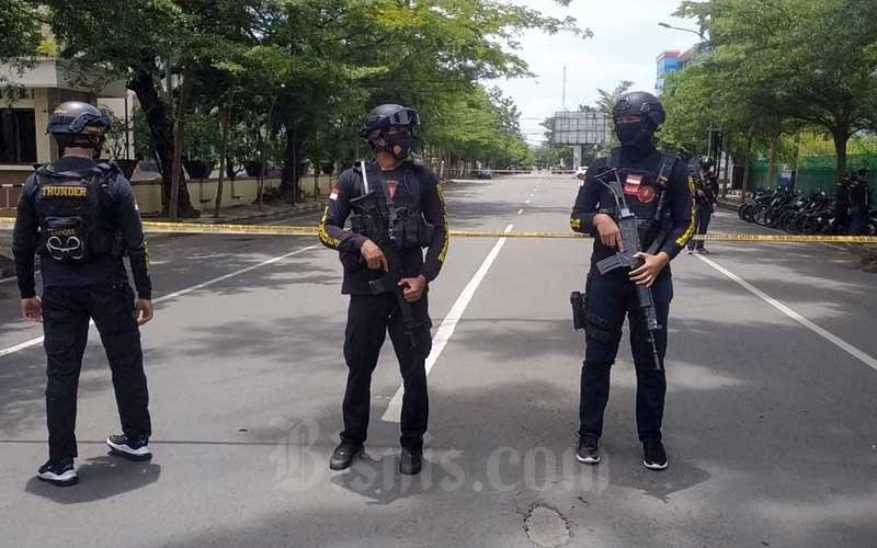 Petugas kepolisian berjaga di lokasi dugaan bom bunuh diri di depan Gereja Katedral Makassar, Sulawesi Selatan, Minggu (28/3/2021). - Bisnis/Paulus Tandi Bone