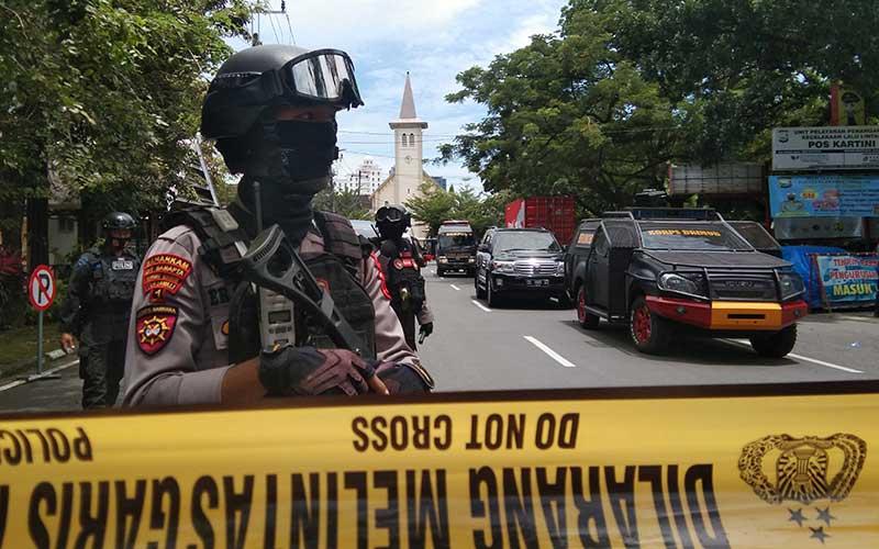 Petugas kepolisian berjaga di lokasi dugaan bom bunuh diri di depan Gereja Katedral Makassar, Sulawesi Selatan, Minggu (28/3/2021). ANTARA FOTO - Arnas Padda