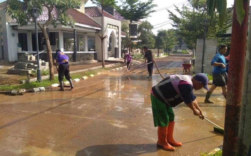 Petugas membersihkan air yang menggenangi akses jalan perumahan? Green Caraka Residence - Bisnis/Dea Andriyawan