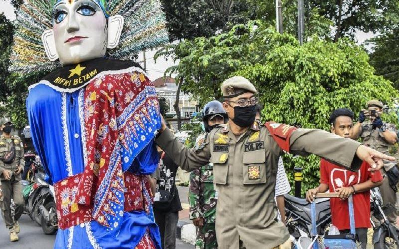 Sejumlah petugas gabungan dari TNI dan Satpol PP saat melakukan razia pengamen ondel-ondel di Jakarta Timur, Rabu (24/3/2021). - Antara