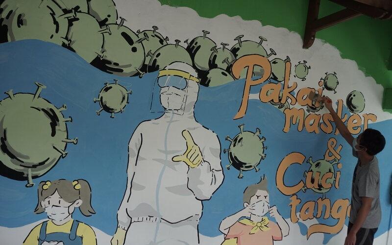 Mahasiswa menggambar mural bertema penanganan Covid-19 di Balai Desa Gawanan, Colomadu, Karanganyar, Jawa Tengah, Kamis (4/3/2021). Mural tersebut sebagai media edukasi masyarakat masyarakat desa pentingnya menerapkan protokol kesehatan untuk mencegah penyebaran Covid-19. - Antara/Mohammad Ayudha.