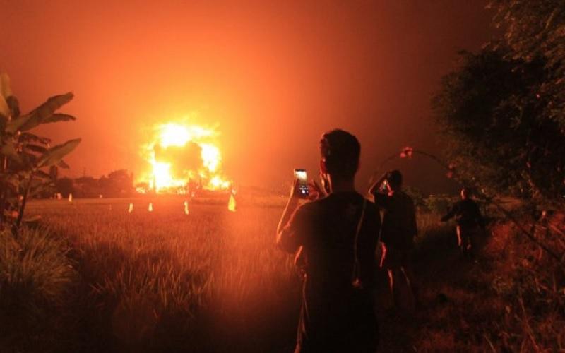 Warga menyaksikan kebakaran di kompleks Pertamina RU VI Balongan, Indramayu, Jawa Barat, Senin (29/3/2021) dini hari. - Antara