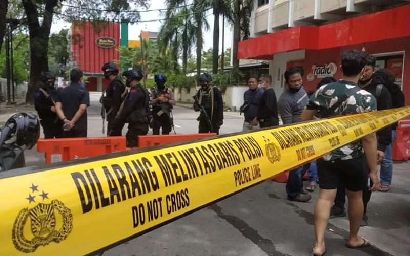 Polisi menutup akses jalan sekitar Gereja Katedral Makassar setelah terjadi ledakan, Minggu (28/3/2021). - Bisnis/Paulus Tandi Bone