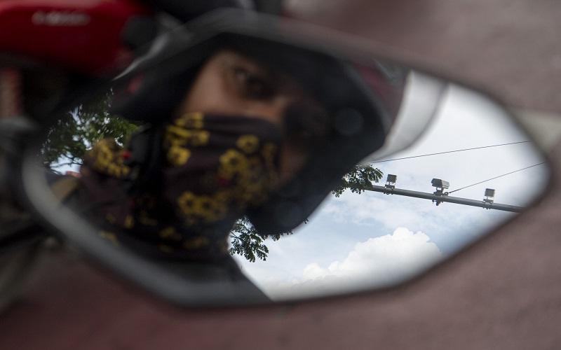 Pengendara melintasi di bawah kamera pengawas atau Closed Circuit Television (CCTV) di kawasan simpang lima DPRD Provinsi Sumatera Selatan, Palembang, Selasa (23/3/2021).  - Antara