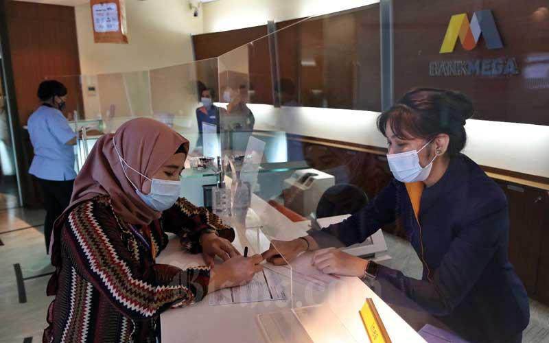 Karyawan melayani nasabah di salah satu kantor cabang Bank Mega di Jakarta, Rabu (11/11/2020). Bank Mega mampu mencatatkan pertumbuhan kinerja positif hingga akhir September 2020, laba sebelum pajak naik 27,7 persen menjadi Rp 2,2 triliun dari posisi tahun sebelumnya sebesar Rp 1,7 triliun. Bisnis - Eusebio Chrysnamurti