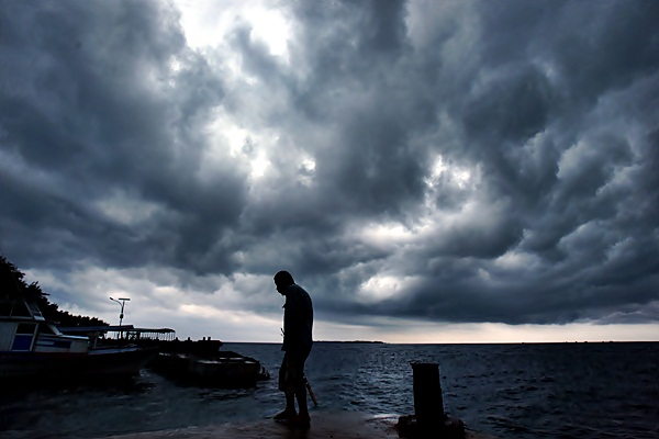Warga beraktivitas dengan latar belakang awan hitam di Dermaga Pulau Pramuka, Kepulauan Seribu, Kamis (23/3). - Antara/Wahyu Putro A