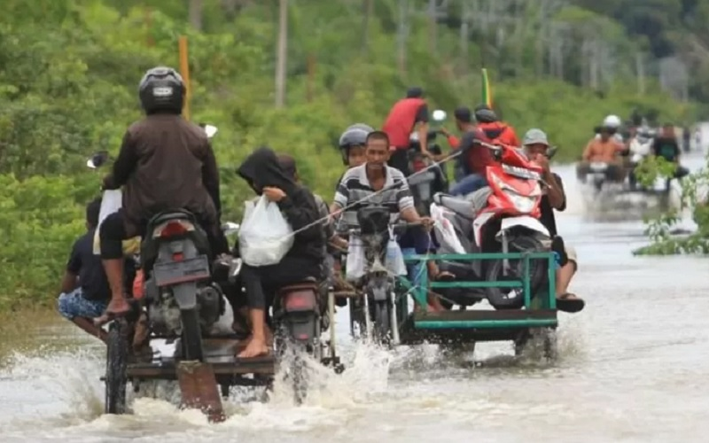 Pengendara memanfaatkan jasa angkut kendaraan roda dua untuk melintasi jalan yang terendam banjir di Desa Layung, Kecamatan Bubon, Aceh Barat, Aceh, Rabu (31/3/2021) - Antara\r\n\r\n