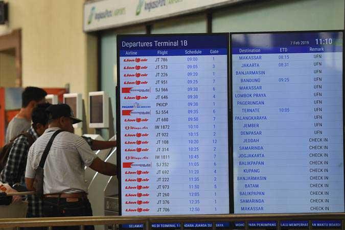Calon penumpang mencetak tiket di samping layar informasi penerbangan di terminal keberangkatan domestik 1B Bandara Internasional Juanda Surabaya, Sidoarjo, Jawa Timur, Kamis (7/2/2019). Bandara tersebut ditutup sementara akibat rusaknya landasan pacu. - ANTARA/Zabur Karuru