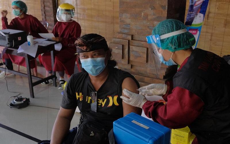 Vaksinator menyuntikkan vaksin Covid-19 kepada warga saat vaksinasi massal di wilayah Sanur, Denpasar, Bali, Senin (22/3/2021). Wilayah Sanur menjadi prioritas vaksinasi Covid-19 dengan menyasar 35.000 warga dan pekerja pariwisata yang ditargetkan selesai pada pertengahan April 2021 karena dipersiapkan sebagai salah satu kawasan zona hijau bebas Covid-19 di Pulau Bali. - Antara/Nyoman Hendra Wibowo.