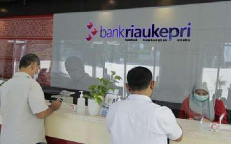 Pegawai Bank Riau Kepri sedang melayani nasabah, dengan menerapkan prokes. Bisnis - Arif Gunawan