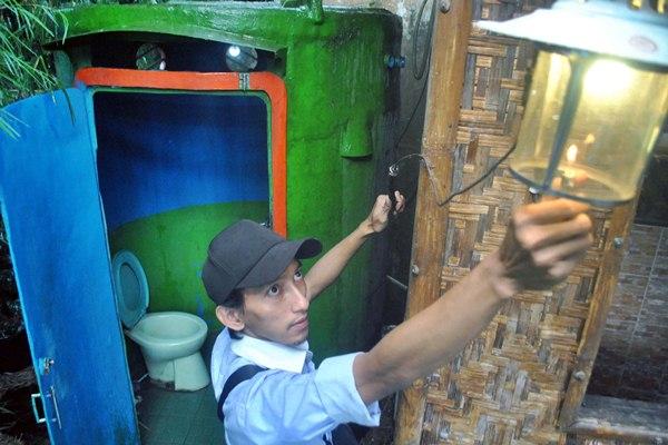 Pekerja menyalakan lampu dari energi biogas yang dihasilkan limbah kotoran manusia di Perumahan Nuansa Indah, Ciomas, Kabupaten Bogor, Jawa Barat, Rabu (5/4). - Antara/Arif Firmansyah