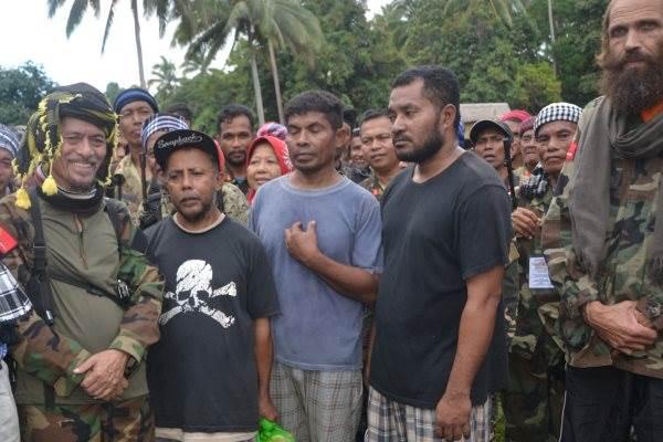 Tiga WNI dan WN Norwegia Kjartan Sekkingstad (kanan) berdiri bersama pemimpin Front Pembebasan Nasional Moro (MNLF) Nur Misuari (kiri) dan anggota kelompok pemberontak lainnya setelah dibebaskan dari kelompok militan Abu Sayyaf di Jolo, Sulu, Filipina, Minggu (18/9/2016). - Reuters/Nickie Butlangan