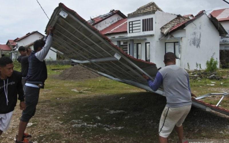 Warga bergotong royong menarik atap rumah yang jatuh di badan jalan akibat diterjang angin kencang di Kota Kupang, NTT, Senin (5/4/2021). BMKG menyebutkan angin kencang dengan kecepatan 45 knot per jam yang terjadi sejak Minggu (4/4) hingga Senin (5/4) tersebut menghancurkan ribuan rumah, menumbangkan sejumlah pohon sehingga mengakibatkan kota Kupang lumpuh total hingga sore ini - Antara Foto/Kornelis Kaha