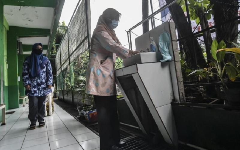 Orangtua murid mencuci tangan sebelum masuk ke dalam kelas saat mengikuti simulasi sekolah campuran tatap muka dan daring (hybrid) di SMP 255, Jakarta Timur, Selasa (30/3/2021). - Antara