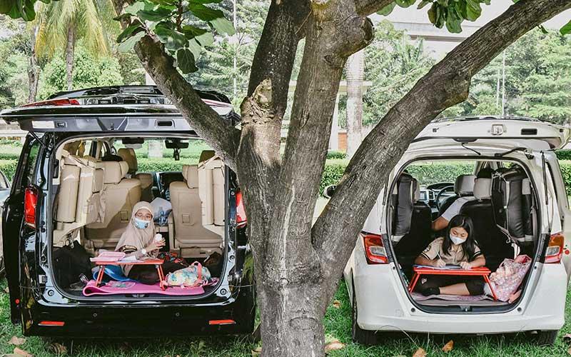 Dua orang murid belajar di dalam bagasi mobilnya masing-masing saat mengikuti sekolah tatap muka secara drive in di Bekasi, Jawa Barat. Antara Foto - Fakhri Hermansyah