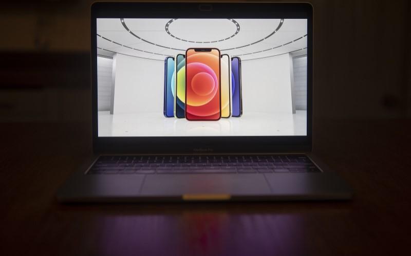 Foto iPhone 12 yang ditampilkan pada layar Macbook Pro. - Bloomberg