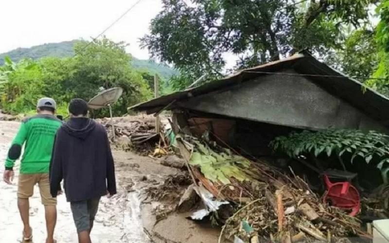 Warga melintas di dekat rumah yang rusak akibat banjir bandang di Adonara Timur, Flores Timur, NTT, Senin (5/4/2021). - Antara