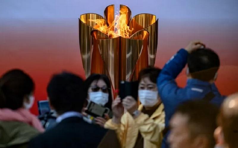 Orang-orang bermasker berfoto di dpean Api Olimpiade Tokyo 2020 yang dipajang di luar stasiun kereta Sendai di Prefektur Miyagi setelah tiba dari Yunani. - Antara/AFP\r\n