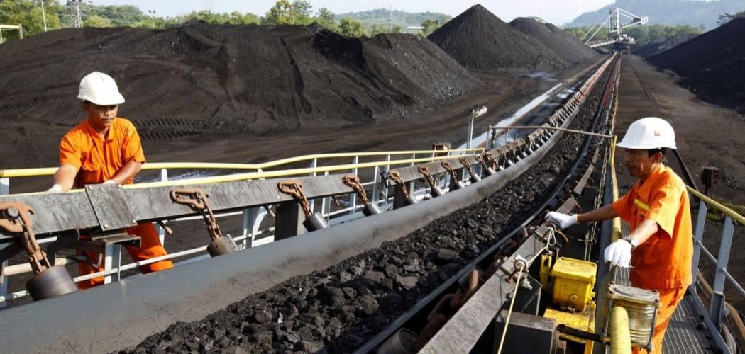 Pekerja melakukan inspeksi pengangkutan batu bara di atas ban berjalan. - Bloomberg / Dadang Tri