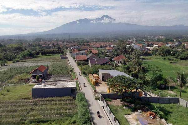 Warga berkendara di jalan di Desa Laladon, Bogor, Jawa Barat, Jumat (28/12/2018). - ANTARA/Yulius Satria Wijaya