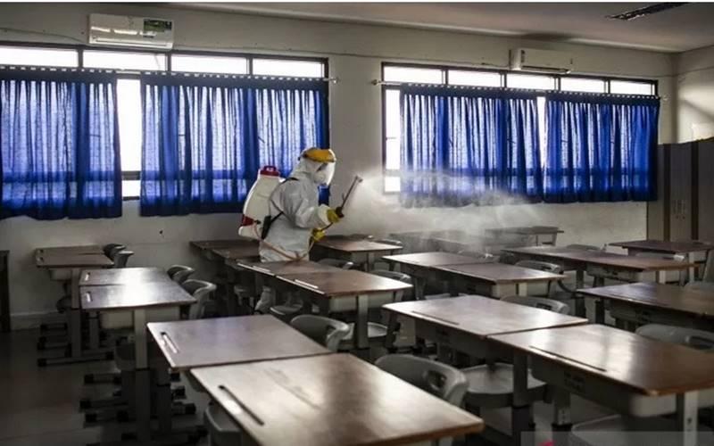 Petugas PMI Kota Jakarta Pusat menyemprotkan cairan disinfektan di ruang kelas SMP Negeri 64 Jakarta, Sawah Besar, Jakarta, Senin (22/6/2020). - Antara
