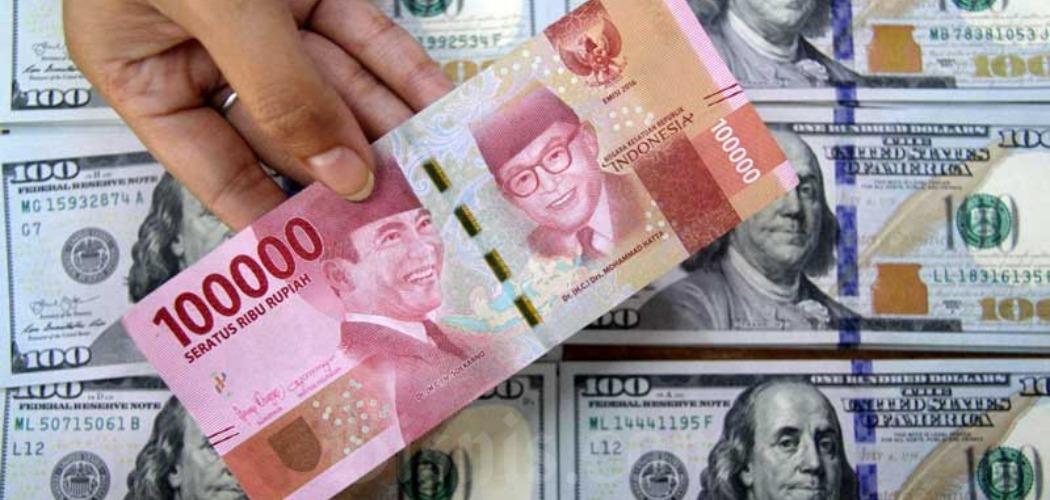 Petugas menunjukkan uang rupiah dan dolar AS di salah satu gerai penukaran mata uang asing di Jakarta, Senin (16/3/2020). - Bisnis/Arief Hermawan P