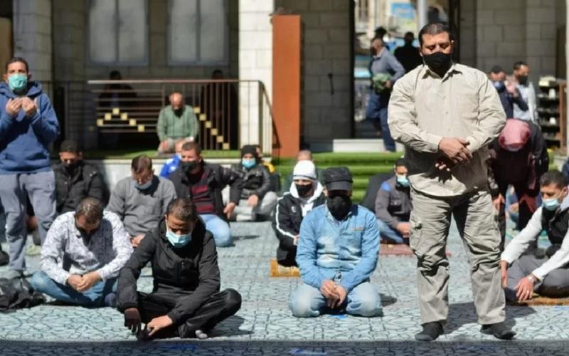 Para pria memakai masker pelindung melakukan ibadah salat Jumat di masjid al-Husseini, saat Yordania mengumumkan peraturan lebih ketat untuk membatasi penyebaran penyakit Covid-19, di Amman, Yordania, Jumat (26/2/2021). - Antara/Reuters