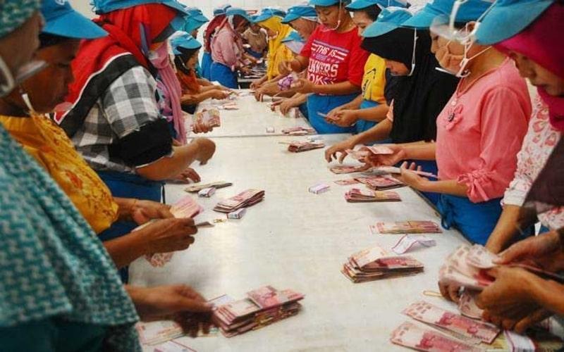 Sejumlah pekerja pabrik rokok menghitung uang Tunjangan Hari Raya (THR) Lebaran saat pembagian di Kudus, Jawa Tengah, Selasa (21/5/2019). - ANTARA/Yusuf Nugroho