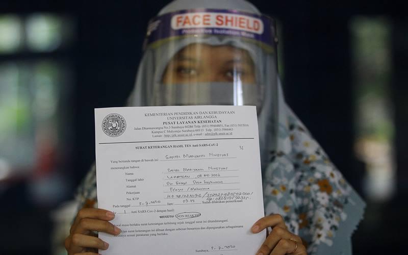 Salah satu peserta memperlihatkan surat keterangan hasil tes cepat (rapid test) sebelum mengikuti Ujian Tulis Berbasis Komputer (UTBK) di Universitas Airlangga (Unair), Surabaya, Jawa Timur, Minggu (5/7/2020). UTBK yang diikuti 31.242 peserta tersebut selain memberlakukan protokol kesehatan juga mewajibkan peserta menunjukkan surat keterangan hasil