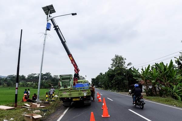 Pekerja memasang lampu penerangan jalan di jalur selatan kawasan Dayeuhluhur, Cilacap, Jawa Tengah, Selasa (30/5). ANTARA FOTO - Hafidz Mubarak
