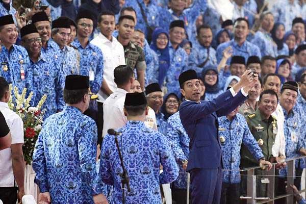 Ilusrasi ASN - Presiden Joko Widodo (kanan) berswafoto dengan aparatur sipil negara saat peringatan Hari Ulang Tahun Ke-47 Korps Pegawai Republik Indonesia (Korpri), di Istora Senayan, Jakarta, Kamis (29/11/2018). - ANTARA/Puspa Perwitasari