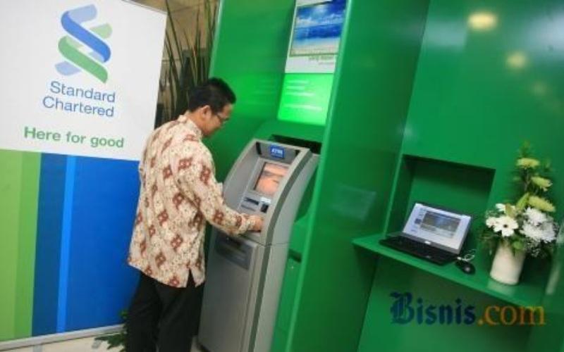 Nasabah melakukan transaksi di salah satu mesin ATM Standard Chartered Bank. - JIBI