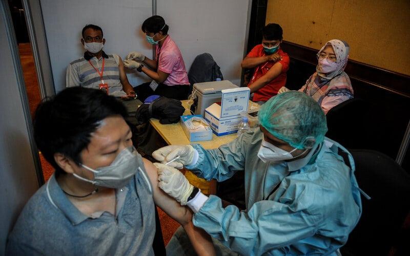 Petugas kesehatan menyuntikkan vaksin Covid-19 kepada pegawai pusat perbelanjaan saat vaksinasi massal di Bandung, Jawa Barat, Kamis (1/4/2021). Sebanyak 2.000 pegawai pusat perbelanjaan di Kota Bandung menjalani vaksinasi Covid-19 pada tahap dua vaksinasi nasional guna memberikan rasa aman dan nyaman bagi masyarakat yang akan berkunjung ke pusat perbelanjaan. - Antara/Raisan Al Farisi.