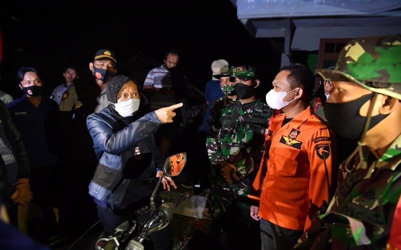 Menteri Sosial Tri Rismaharini (kiri) berbincang dengan Bupati Lumajang Thoriqul Haq (kedua kanan) ketika meninjau lokasi terdampak gempa di Desa Kali Uling, Lumajang, Jawa Timur, Minggu (11/4/2021). Dalam kunjungannya, Mensos Tri Rismaharini memberikan bantuan kepada warga yang terdampak gempa dan meminta pemerintah setempat segera mencari lokasi yang aman untuk dibangun posko pengungsian. - Antara/Zabur Karuru.