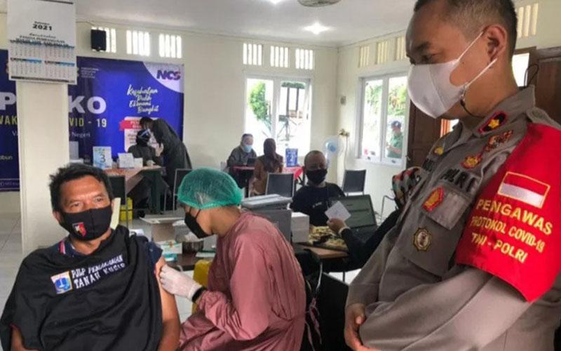 Kepala Polsek Metro Kebayoran Lama Komisaris Polisi Donni Bagus Wibisono (kanan) meninjau vaksinasi bagi petugas pemakaman TPU Tanah Kusir di Jakarta pada Sabtu (10/4/2021)./Antara - Polsek Kebayoran Lama