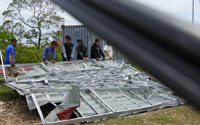 Warga bergotong royong menarik atap rumah yang jatuh di badan jalan akibat diterjang angin kencang di Kota Kupang NTT, Senin (05/04/2021). - Antara\r\n