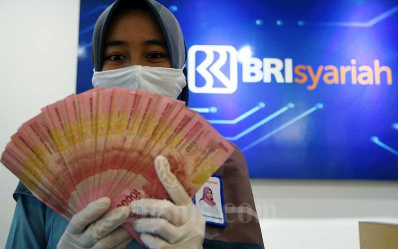 Ilustrasi karyawan BRI menunjukkan uang rupiah  Rabu (29/7/2020). Pemerintah kembali membuka pendaftaran BLT UMKM 2021 dengan nominal bantuan Rp1,2 juta Bisnis - Abdurachman